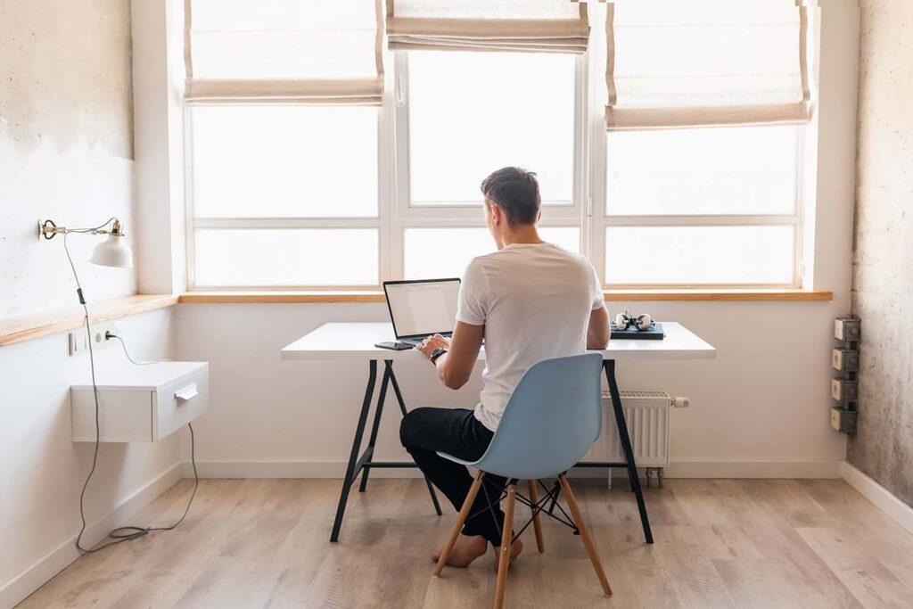 jeune homme de dos à son bureau en télétravail